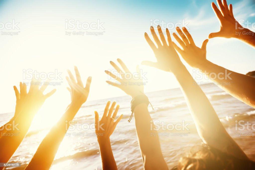 Amigos de viaje con las manos y puesta de sol mar - foto de stock