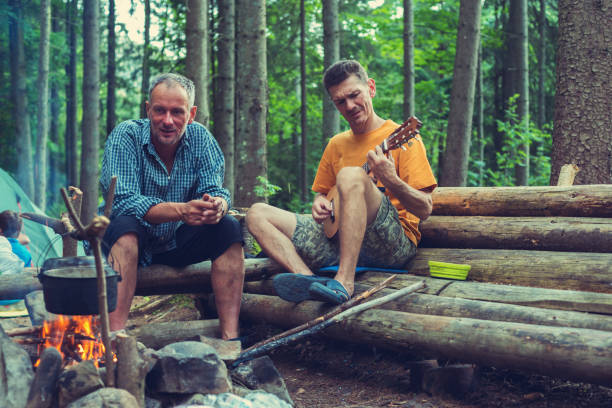 freunde, reisende neben einem lagerfeuer sitzen - ukulele songs stock-fotos und bilder