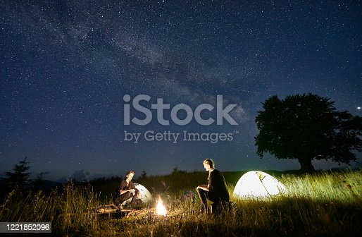 678554980 istock photo Friends travellers spending time in the mountains sitting around bonfire in camping under beautiful starry sky 1221852096