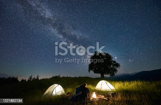 678554980 istock photo Friends travellers spending time in the mountains sitting around bonfire in camping under beautiful starry sky 1221852134