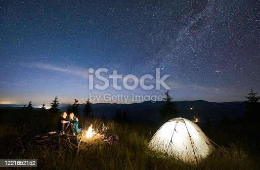 678554980 istock photo Friends travellers spending time in the mountains sitting around bonfire in camping under beautiful starry sky 1221852152