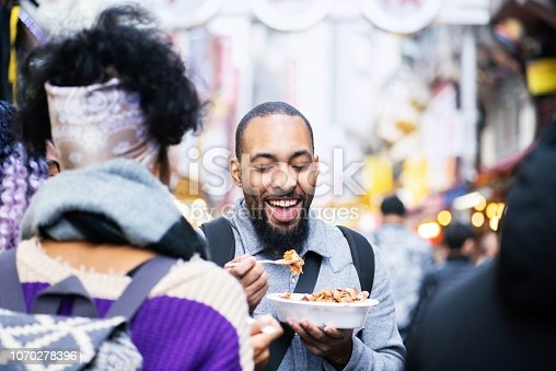 Three millennial travelers trying street foods and snacks while travelling in Japan