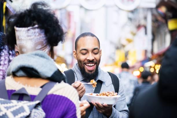 freunde versuchen lokale köstlichkeiten beim erkunden ihren bestimmungsort - streetfood stock-fotos und bilder