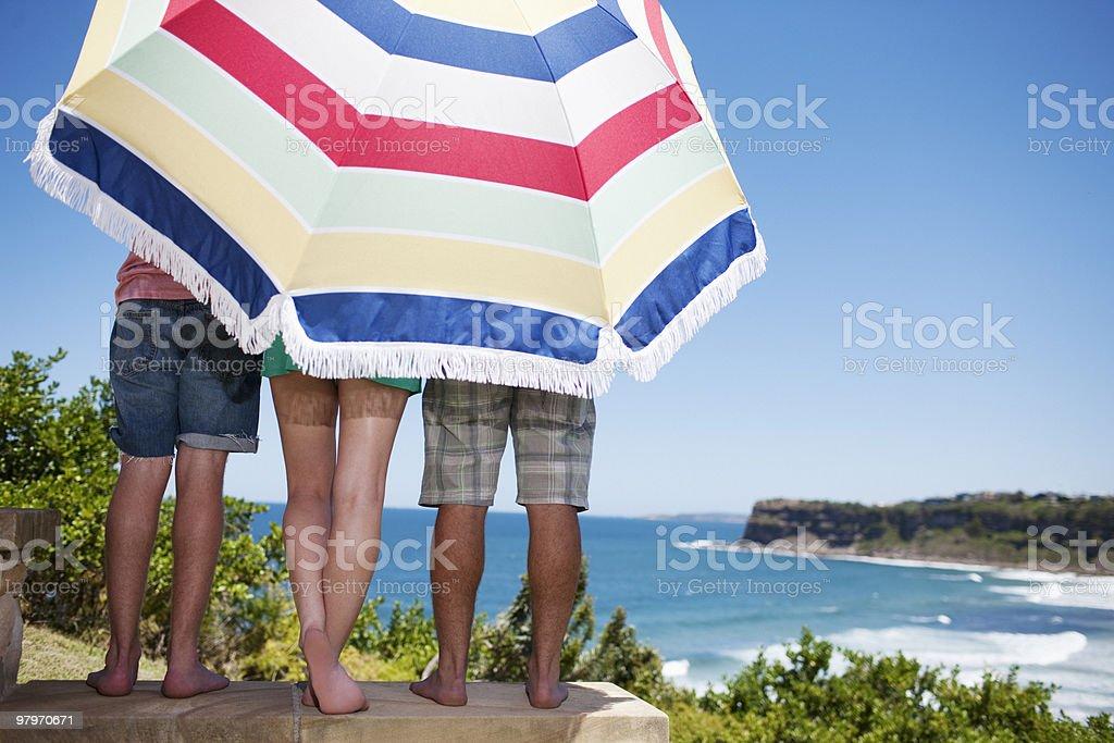 Friends under beach umbrella on patio overlooking ocean royalty-free stock photo