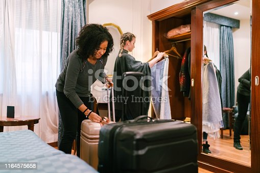 Girls just arriving in the hotel and unpacking clothes