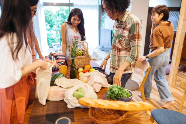 freunde packen ihre wiederverwendbaren einkaufstaschen aus, nachdem sie im supermarkt für die home-party eingekauft haben - jamaikanische party stock-fotos und bilder