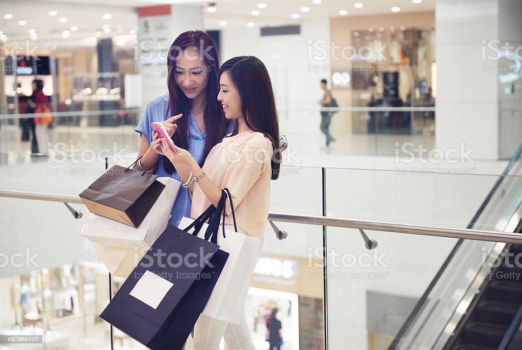 Friends Update Social Media Status in Hong Kong Luxury Mall stock photo