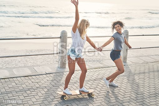 Shot of a woman pulling her friend on a skateboard while out on the promenade