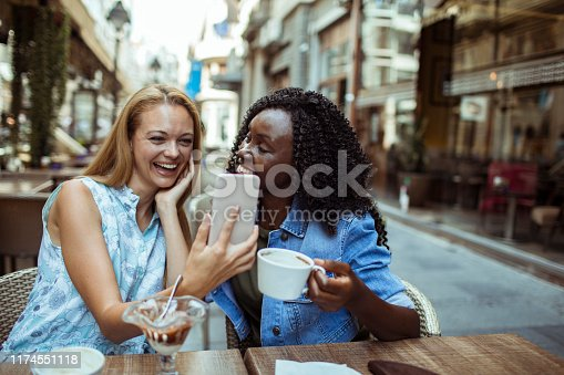 Close up of two friends using a phone while sitting in a cafe