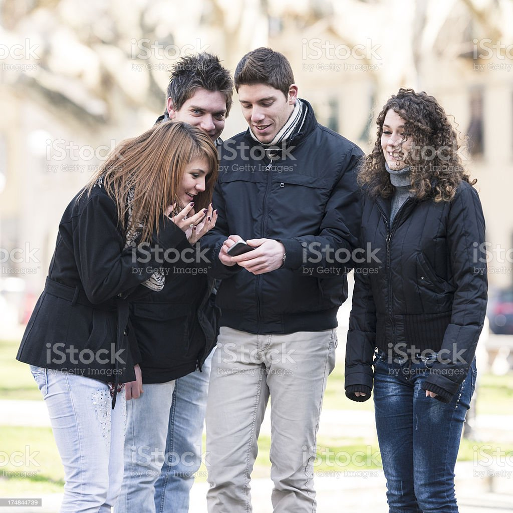 friends using a smarthpone outdoors royalty-free stock photo