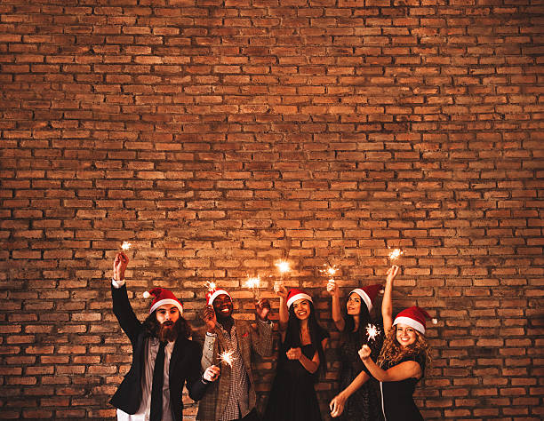 friends using a sparkler togetherness for christmas stock photo