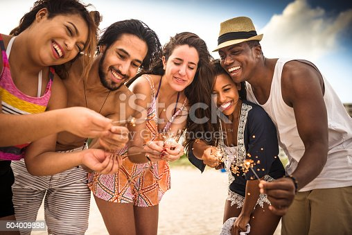 471113366istockphoto friends using a sparkler togetherness on the beach 504009898
