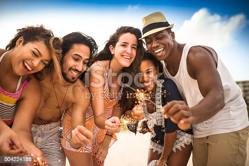 471113366istockphoto friends using a sparkler togetherness on the beach 504224188