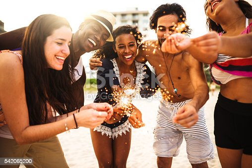 471113366istockphoto friends using a sparkler togetherness on the beach 542065200