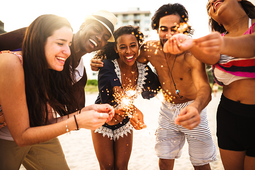 471113366 istock photo friends using a sparkler togetherness on the beach 542065200
