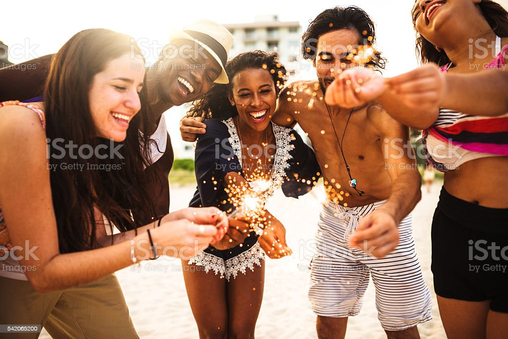 friends using a sparkler togetherness on the beach stock photo