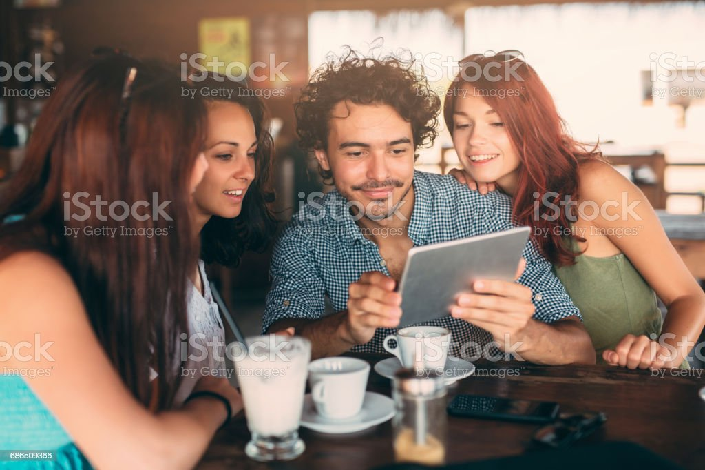 Vrienden met behulp van een tablet in het café royalty free stockfoto