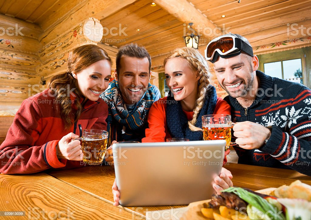 Friends using digital tablet Group fo friends sitting in a mountain restaurant after skiing, enjoying beer and using a digital tablet together. Adult Stock Photo