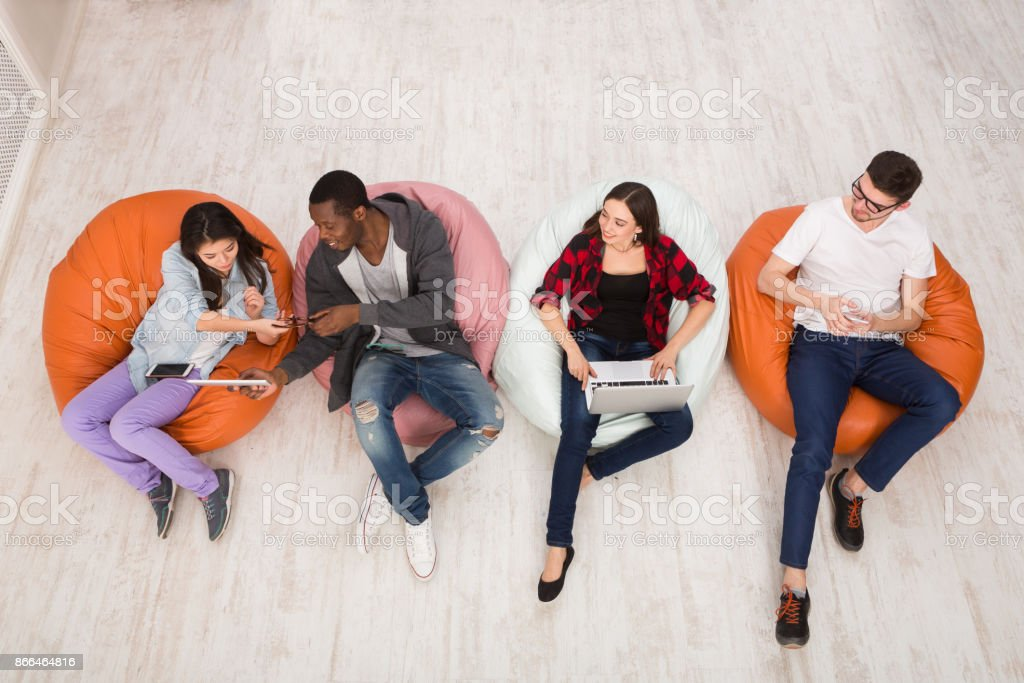 Friends using gadgets, sitting indoors in line stock photo