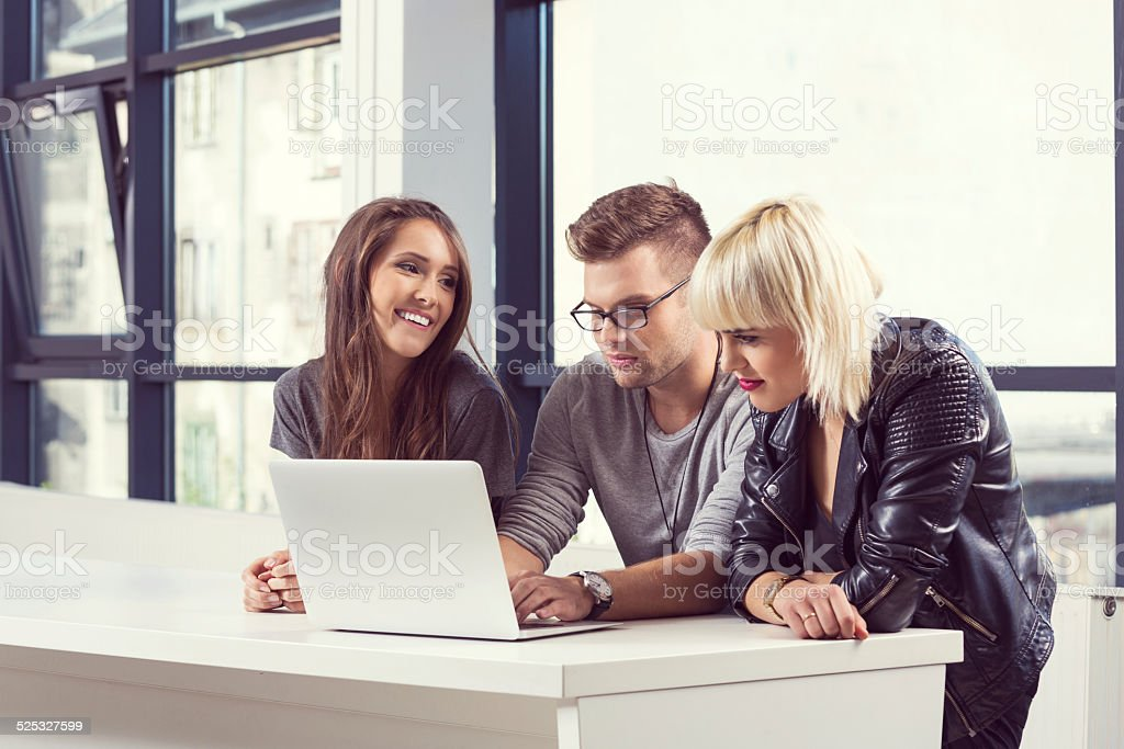 Friends using laptop together Three cheerful student sitting at the table at university and using laptop together. Adult Stock Photo