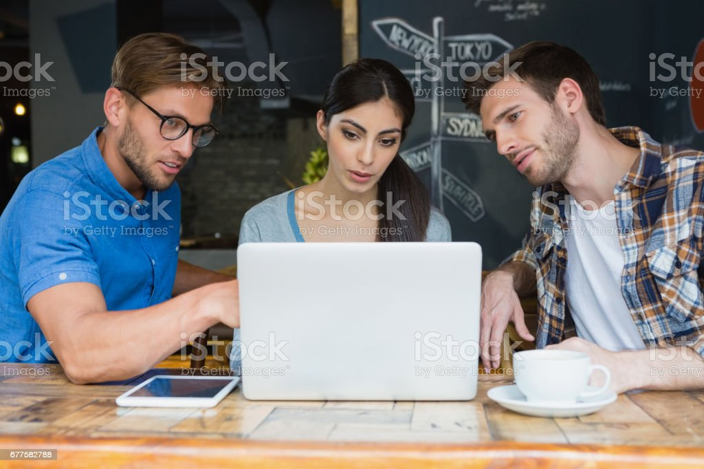 Friends using laptop while having coffee royalty-free stock photo