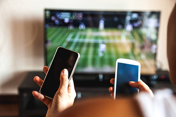 friends using mobile phone during a tennis match - downloading stock pictures, royalty-free photos & images
