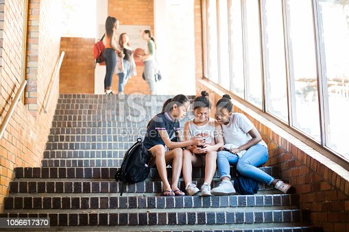 Multi-ethnic friends using mobile phone on steps. Full length of students are in casuals. Females are sitting in high school.