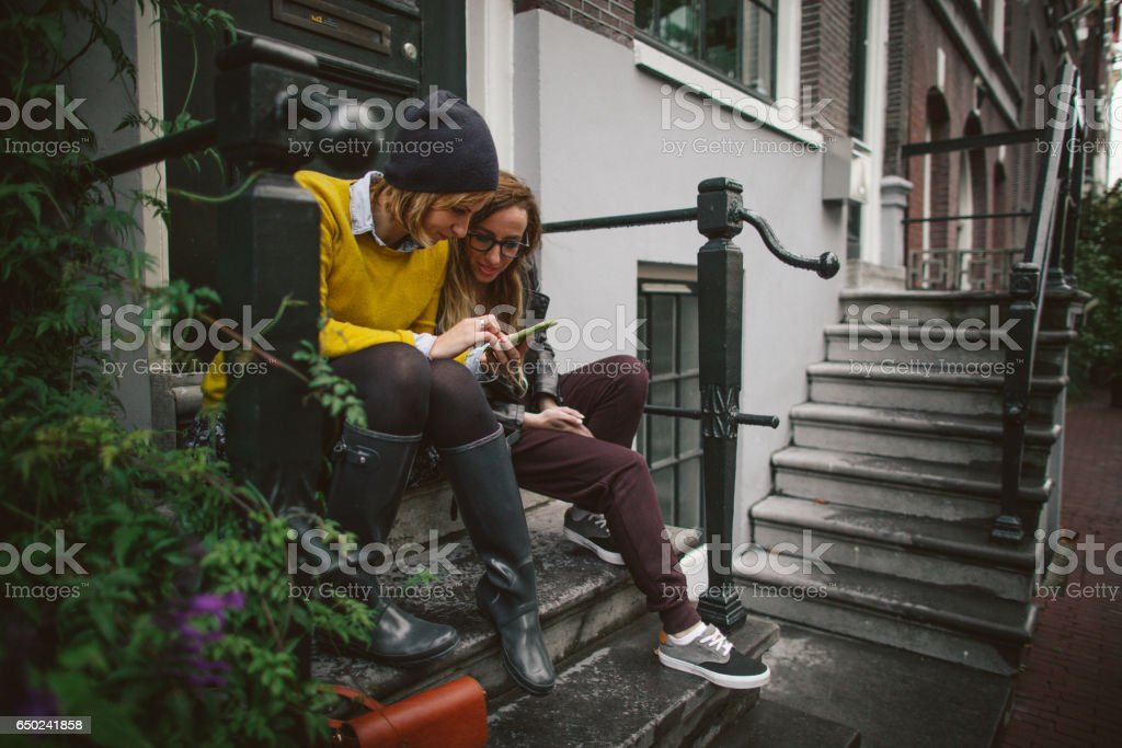 Friends using mobile phone stock photo