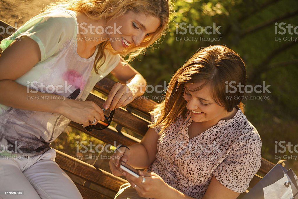 Friends using smart phone in park royalty-free stock photo
