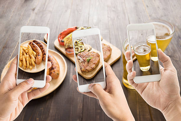 friends using smartphones to take photos of food. stock photo