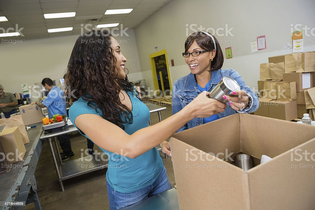 Friends volunteering to sort donation at food bank stock photo