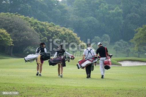 A group of friends talk to each other as they walk with their golf bags down the fairway