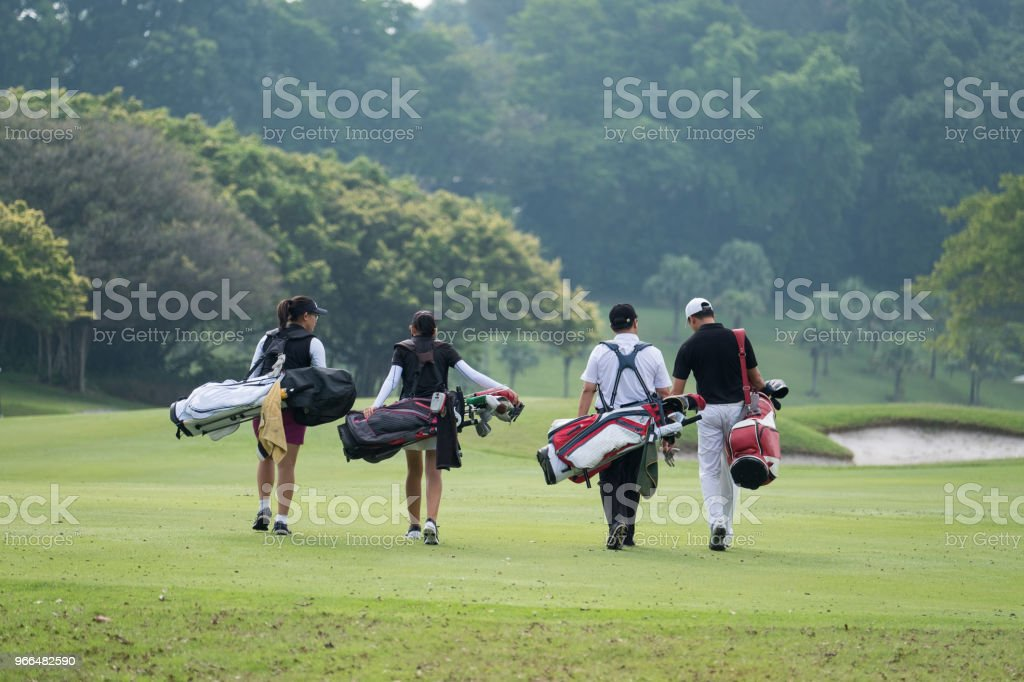 Friends walk together down the fairway stock photo