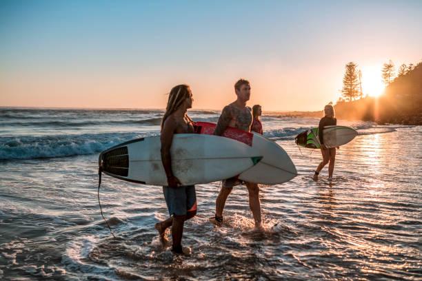 Freunde zu Fuß entlang der Küste mit Surfbrettern – Foto