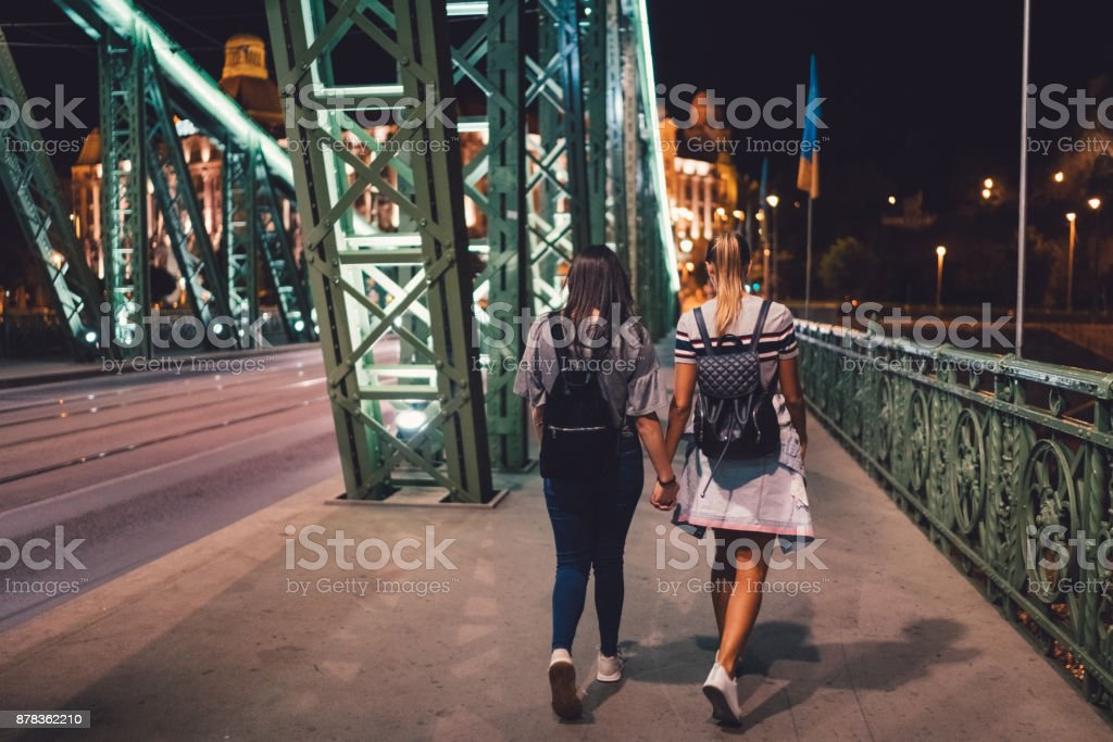 Friends walking at night along Liberty bridge stock photo