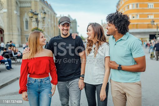 1051098428istockphoto Friends walking during tral in the city 1161737459
