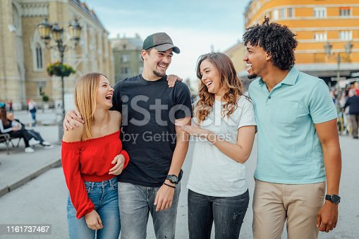 1051098428istockphoto Friends walking during tral in the city 1161737467