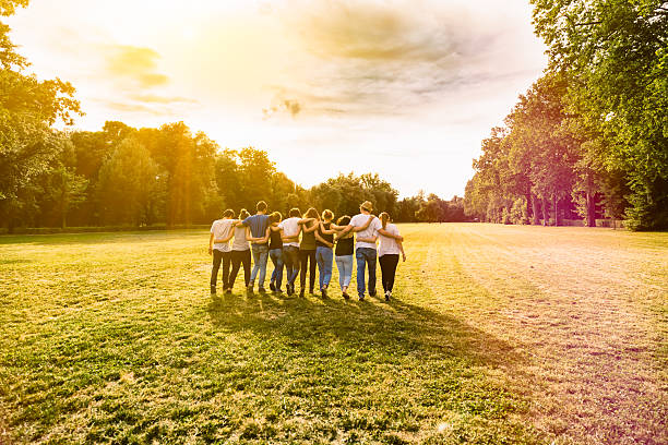 Friends walking in a park at sunset arm in arm stock photo