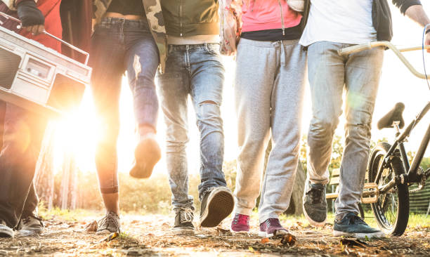 Friends walking in city park with backlight and sunflare halo - Millenial friendship concept and multiracial young people on alternative fashion having fun together - Leg view with soft blurred motion stock photo