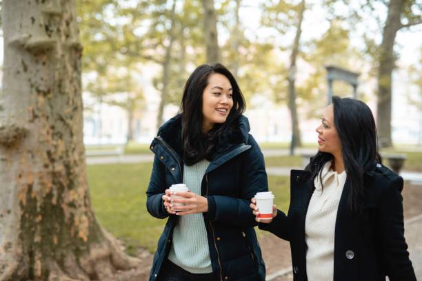Freunde, die zu Fuß in den Park bei einer Tasse Kaffee – Foto