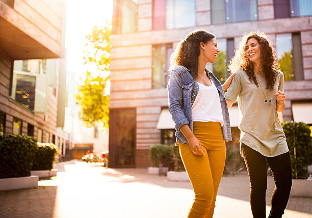 Friends Walking In Urban Area Together stock photo