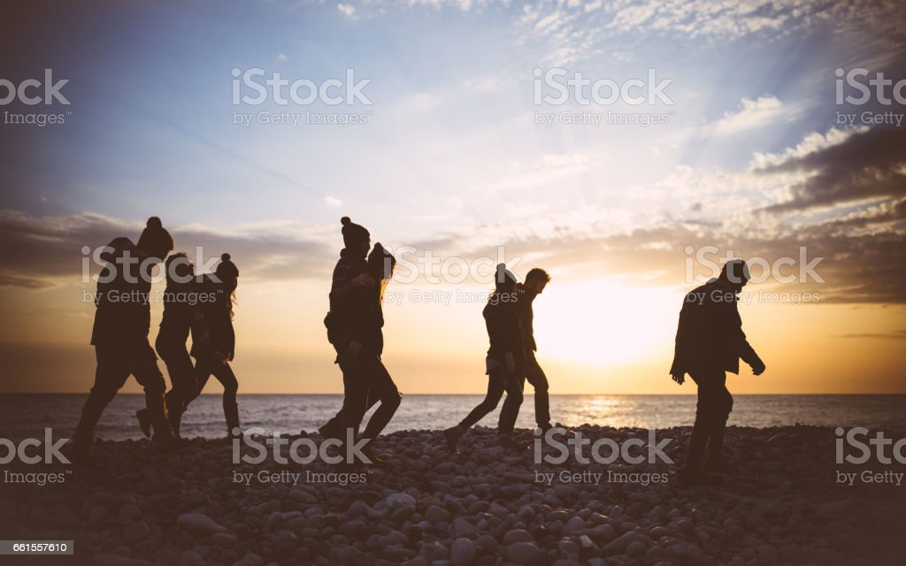 Friends walking on the beach at sunset in the winter stock photo