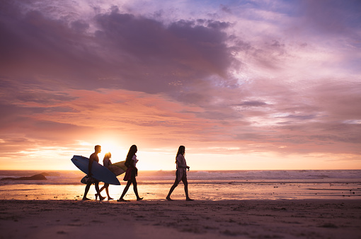 Friends walking on the beach in the evening