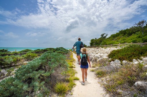 Couple walking to the beach with sand dunes. People hiking on Beautiful Florida beach. Bahia Honda State Park, Florida Keys, FLorida,USA.