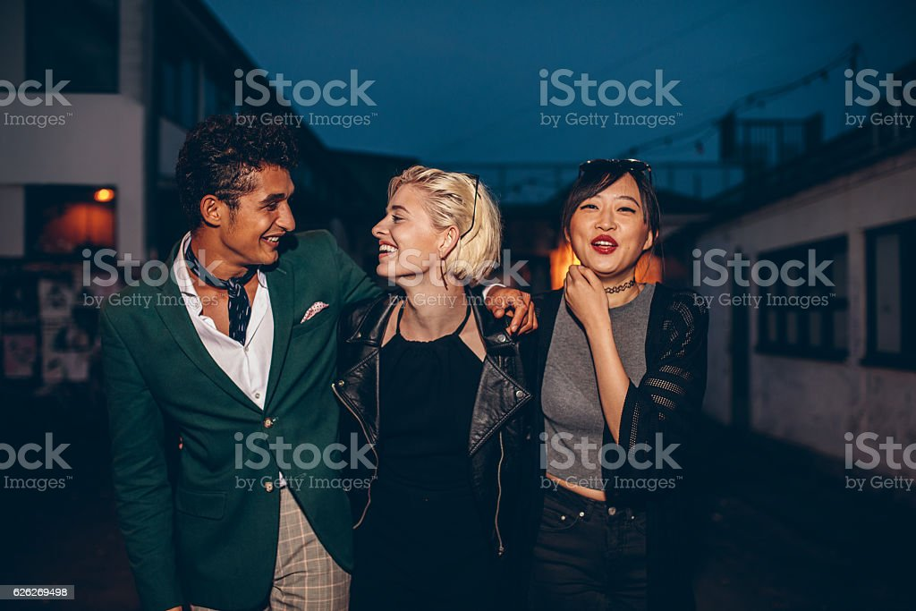 Friends walking on the street at night stock photo