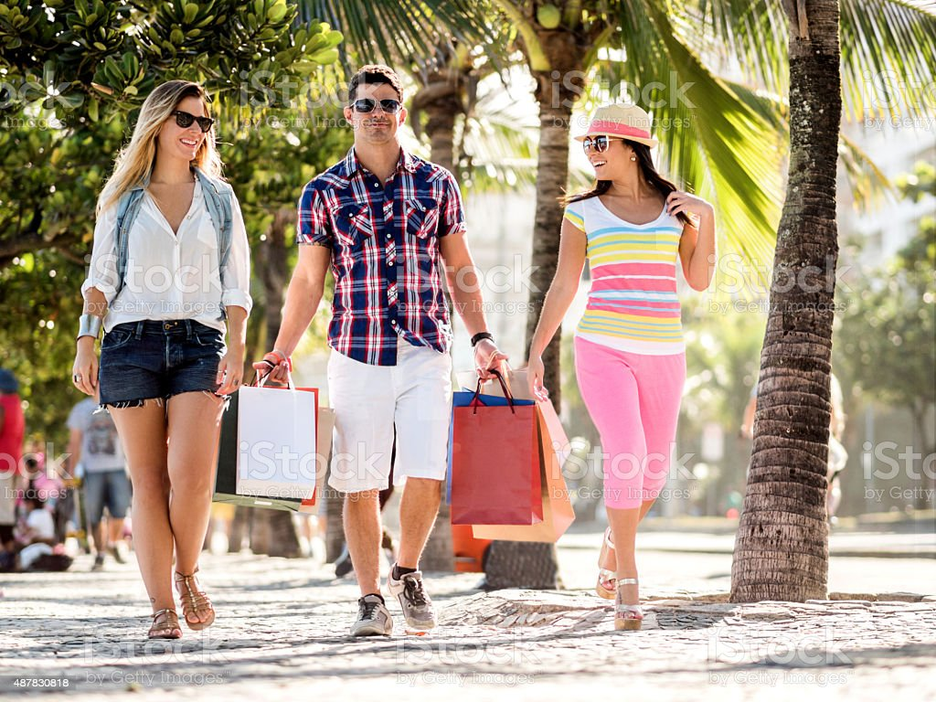Friends walking on the street while coming back from shopping. stock photo