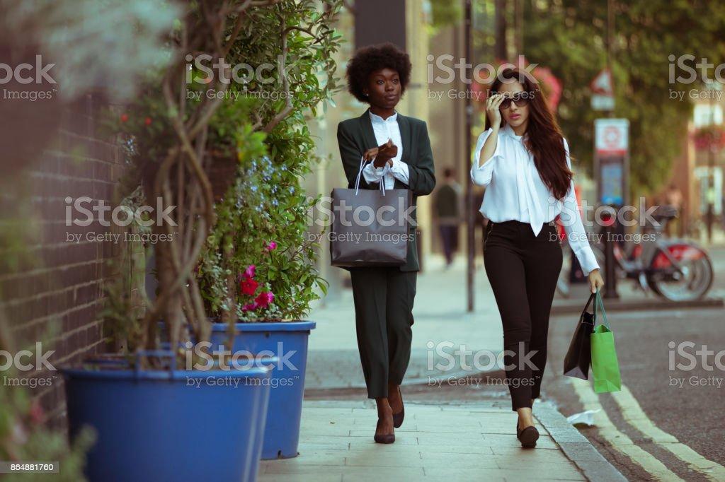 Amigos caminando pasado afterwork, tiendas para ir a casa juntos. - foto de stock