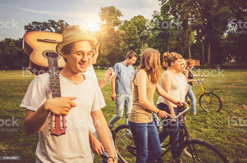 Friends walking together in a field stock photo