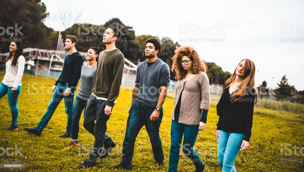 friends walking together in a park royalty-free stock photo