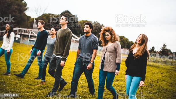 Friends Walking Together In A Park Stock Photo - Download Image Now